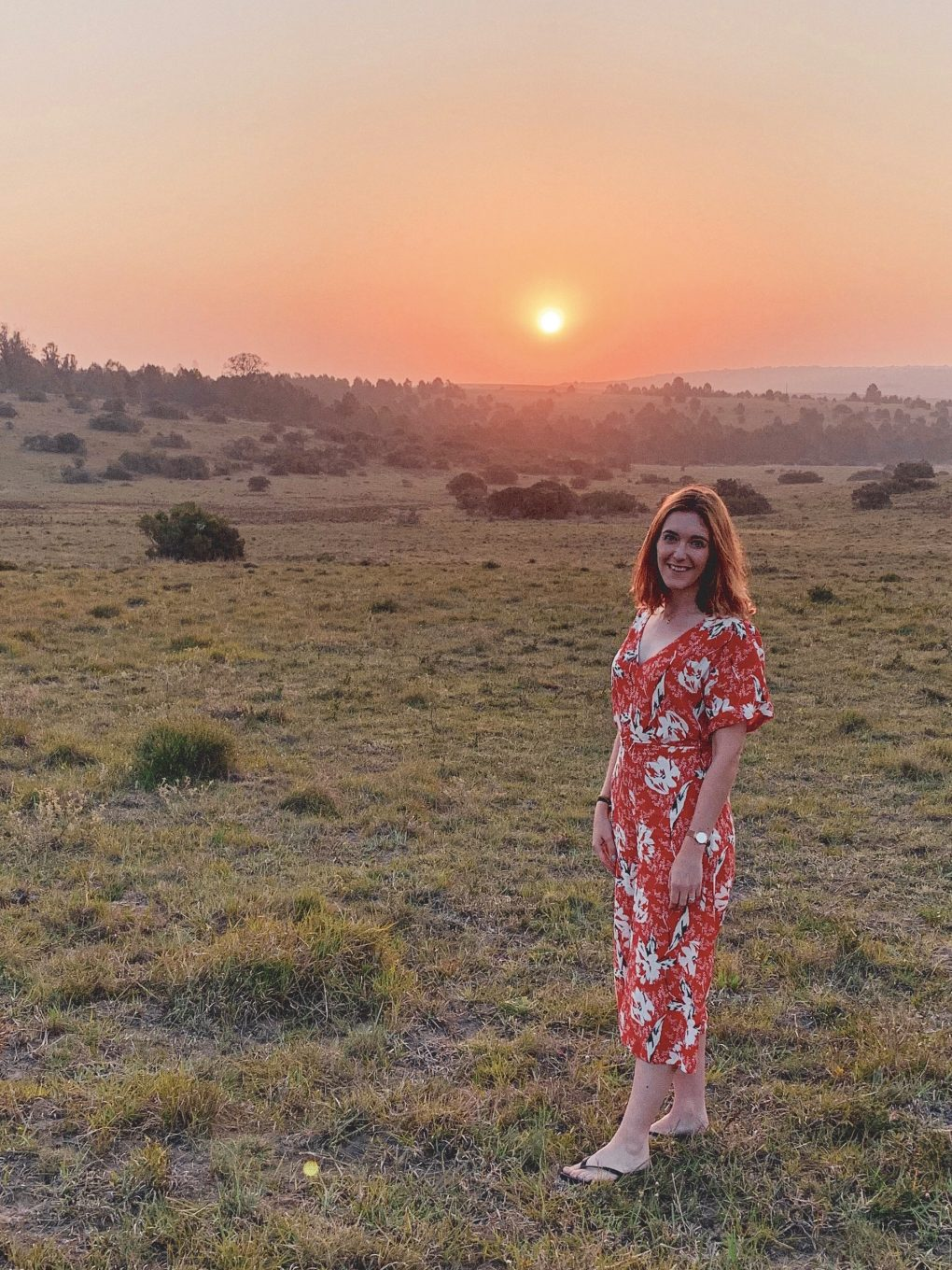 I'm standing in the National Park wearing a red 3/4 length jumpsuit with flip flops smiling at the camera. The sun is setting in the background and there are zebra in the distance. Taken in South Africa.